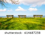 Small photo of 3 lonely empty bench on beautiful green grass over sea looking with nice blue sky clouds.