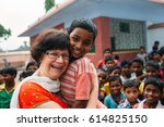 Small photo of India - March 11, 2015: Missionary woman hugging poor rural indian child in the school