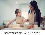 mother and daugthter cooking... | Shutterstock . vector #614872754