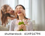 Happy mother's day! Child daughter congratulates mom and gives her flowers tulips. Mum and girl smiling and hugging. Family holiday and togetherness.