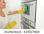 smiling female person cleaning... | Shutterstock . vector #615027860