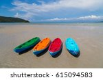Colorful Canoes On The Beach.