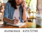 young woman writing on notebook. | Shutterstock . vector #615172760