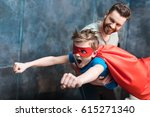 father holding son in superhero ... | Shutterstock . vector #615271340