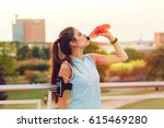 Stock photo young woman with earphones resting and drinking from a plastic bottle after running cityscape 615469280