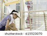 Small photo of Woman suffering from ankle issue, accident, sprained. Unhappy young woman sitting on the mat, grabbing an ankle. Beginner doing wrong exercise without coacher.