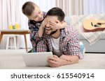 father and his son with tablet... | Shutterstock . vector #615540914