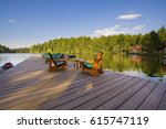 muskoka chairs on a wood deck... | Shutterstock . vector #615747119