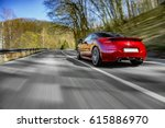 Stock photo generic red sports car driving fast on the open road 615886970