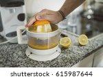 man preparing a orange juice in ... | Shutterstock . vector #615987644