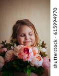 little girl holding a bouquet... | Shutterstock . vector #615994970