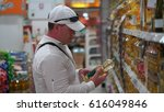 man buys sunflower oil in a... | Shutterstock . vector #616049846