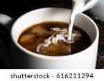 pouring cream into a cup of... | Shutterstock . vector #616211294