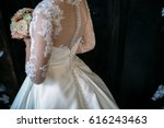 the bride in a white dress is... | Shutterstock . vector #616243463