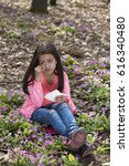 Small photo of Girl with allergic rhinitis sitting among primroses. Selective focus