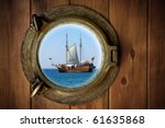 Close-up of a boat closed porthole with view to an old galleon - stock photo