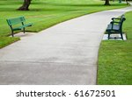 Two green metal benches across a large concrete pathway in a park - stock photo