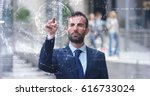 a businessman in a suit uses... | Shutterstock . vector #616733024