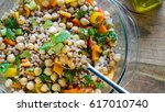 Small photo of A salad consisting of farro, garbanzo beans, bell peppers, and spring onions served with olive oil on wooden table- healthy vegan eating concept