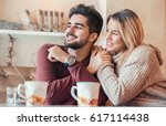 beautiful young couple sitting... | Shutterstock . vector #617114438