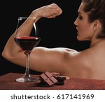 Small photo of Red wine glass with chocolate and female bodybuilder showing muscles