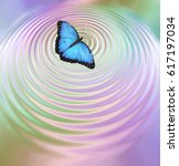 Stock photo the butterfly effect big blue butterfly appearing to create ripples in pink green water surface 617197034
