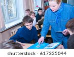 schoolchildren sit at their... | Shutterstock . vector #617325044