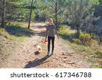 Stock photo teen girl walking with a white maltichon dog in forest track 617346788