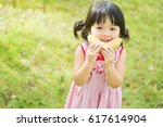happy little asian girl eating... | Shutterstock . vector #617614904