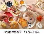 rich breakfast table. pouring... | Shutterstock . vector #617687468