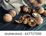 some walnuts on a black wooden... | Shutterstock . vector #617717330