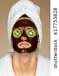 Small photo of Man with chocolate mack and kiwi slices on eyes. Portrait of handsome man receiving spa treatments. Skin care concept