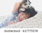 Stock photo cute asian child playing with siberian husky puppy on white basket chair 617775278