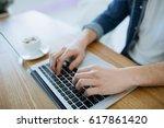 man working on a macbook or... | Shutterstock . vector #617861420