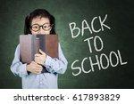 cute schoolgirl looking at... | Shutterstock . vector #617893829