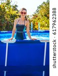 Small photo of Fun weekend alfresco. Portrait of happy healthy woman in blue swimwear in the swimming pool in sunglasses