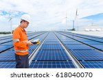engineer checking solar panels... | Shutterstock . vector #618040070
