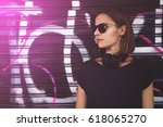 Small photo of Young attractive female hipster with the bob cut standing near the graffiti wall. Mock up, copy space for your text.