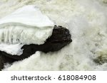 icy rock in turbulent waters | Shutterstock . vector #618084908