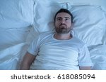 stressed man trying to sleep in ... | Shutterstock . vector #618085094
