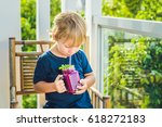 the boy holds smoothies from a... | Shutterstock . vector #618272183