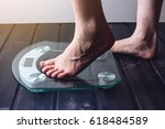 Stock photo female feet standing on electronic scales for weight control on wooden background the concept of 618484589
