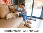 asia woman reading book on sofa ... | Shutterstock . vector #618785960