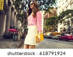 Stock photo beautiful brunette young woman wearing nice skirt and pink blouse yellow purse walking on the 618791924