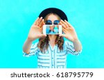 Small photo of Fashion woman is taking photo self portrait on a smartphone in the city closeup screen over colorful blue background