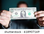 a man holds a u.s. 1 one dollar. | Shutterstock . vector #618907169