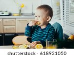 the child in the kitchen eating ... | Shutterstock . vector #618921050