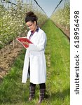 Small photo of Young woman agronomist in white coat standing in orchard with blossoming trees and writing notes