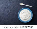 Greek yogurt in blue bowl on black table top view.