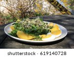 Small photo of Dish with chicken spring herbs, Glechoma and Aegopodium and lentil sprouts. Boiled potatoes, eggs and green herbs on a plate outdoors in spring garden